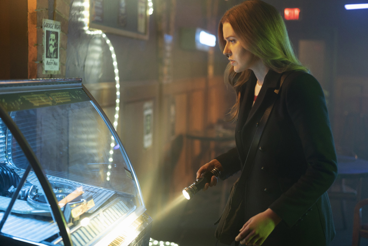 Nancy Drew with her flashlight investigating a jukebox