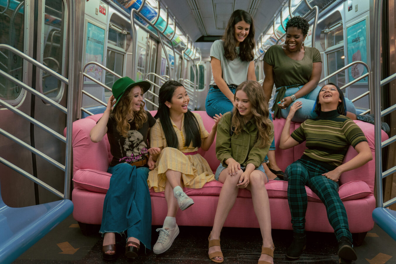 Lara Jean and friends on a pink couch in the NYC subway in To All the Boys 3.